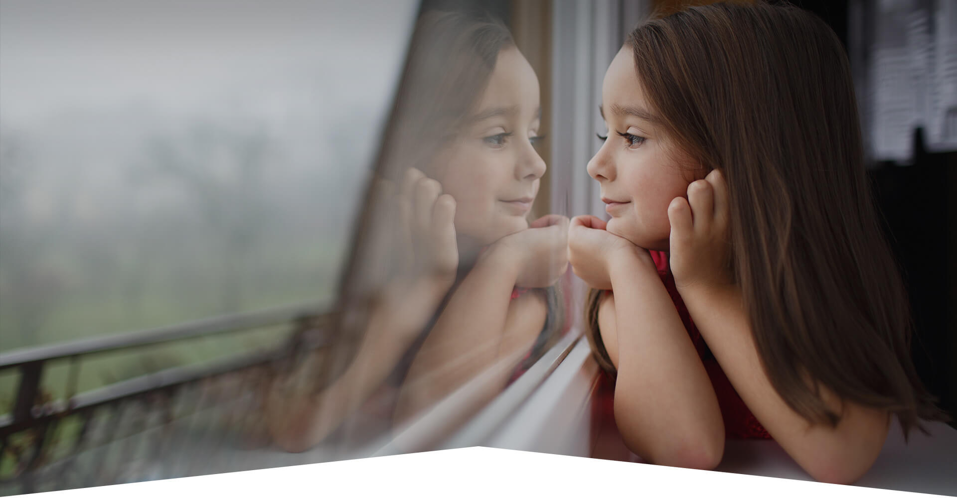 Photo d'atmosphère montrant une enfant regardant par la fenêtre, ainsi que son reflet